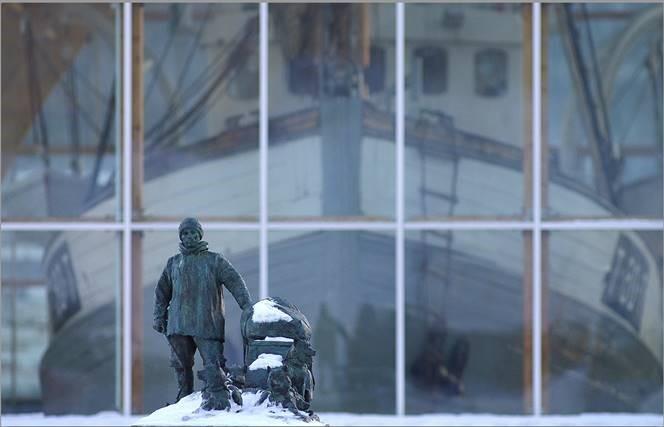 statue av mann med hundeslede dekket i snø