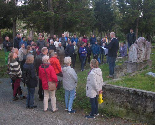 Gruppe mennesker samlet rundt det en gravstein